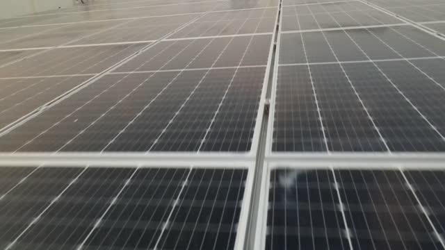 vídeos de stock, filmes e b-roll de vistas aéreas de drones movendo-se muito perto de large solar panel array 4k vista aérea da fazenda de painéis solares (célula solar) com luz solar. - energia solar