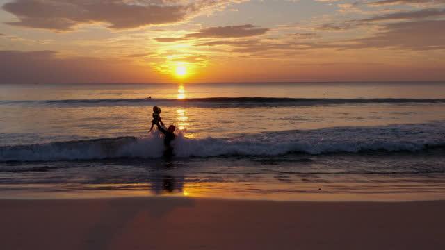 vidéos et rushes de vue aérienne de drone, silhouette du père enseignant nager avec le petit garçon âge 12 mois ensemble à l'extérieur un été au coucher du soleil. concept de vacances. - 12 17 mois