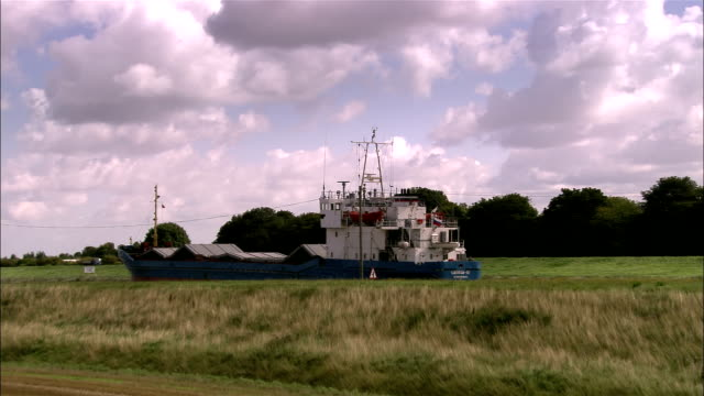 aerial dry freighter sailing down nene obscured by field toward swing bridge/ sutton bridge, england - swing bridge stock videos & royalty-free footage