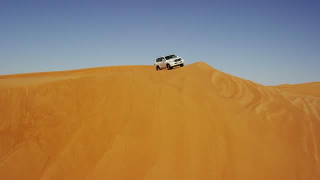 aerial dubai drone view of desert safari vehicles - sanddüne stock-videos und b-roll-filmmaterial