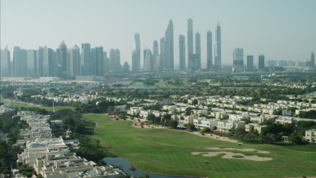 aerial dubai skyline skyscrapers emirates hills residential golf - golf course stock videos & royalty-free footage