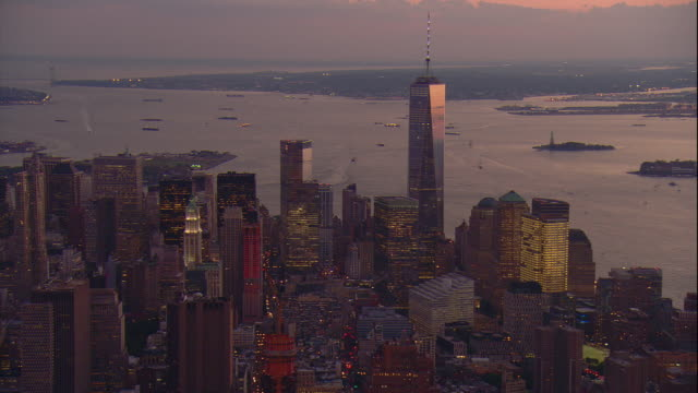 vídeos de stock, filmes e b-roll de aerial -early evening shot of lower manhattan and the freedom tower with new york harbor in the bg. - torre da liberdade nova iorque