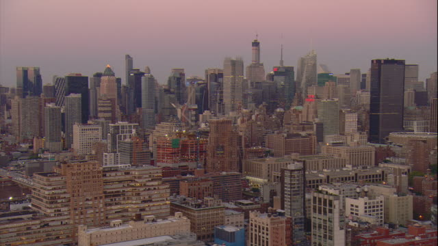 aerial -early evening shot over chelsea low-rise buildings with mid-town manhattan skyline behind. - chelsea new york stock videos & royalty-free footage