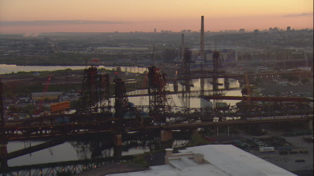 Aerial -Early morning dolly shot of industrial development and traffic along the Pulaski Skyway bridge.