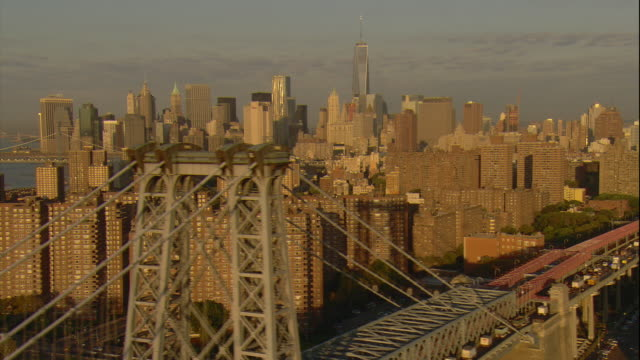 vídeos de stock, filmes e b-roll de aerial -early morning low pass over the williamsburg bridge with buildings of the lower east side in fg and lower manhattan skyline including the freedom tower behind. - williamsburg new york