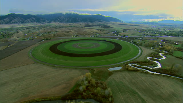 vídeos de stock, filmes e b-roll de aerial early morning sot of crop irrigation circle and mountains outside of bozeman, mt - bozeman