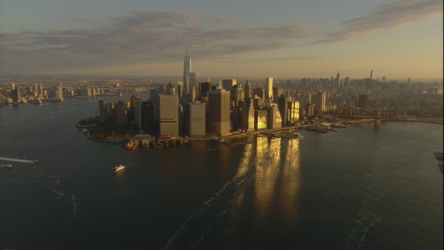aerial -early morning view of lower manhattan and the freedom tower from over the east river. - east river stock videos & royalty-free footage