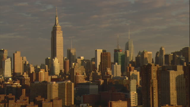Aerial -Early morning view of the mid-town Manhattan skyline including the Empire State Building, as seen from low over the East River.