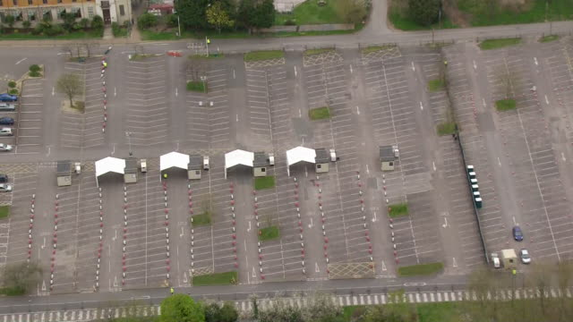 aerial empty drive through coronavirus testing centre for nhs staff set up in car park - parking stock videos & royalty-free footage