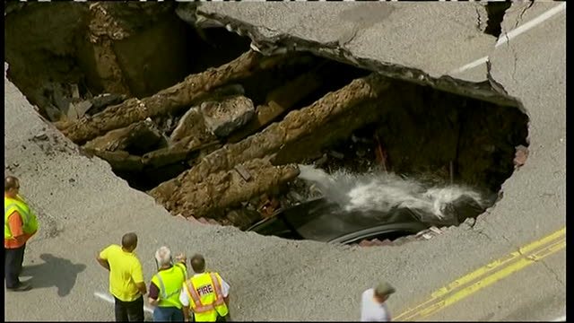 aerial establishing shot of a car in a sinkhole in toledo, ohio. - produced segment stock videos & royalty-free footage