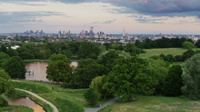 aerial establishing shot of fields and ponds of hampstead heath at sunset - drone point of view stock videos & royalty-free footage