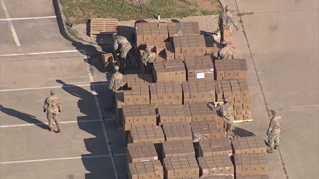 aerial establishing shot of members of the national guard at a food bank distribution area in dallas, texas during the covid-19 outbreak. - healthcare and medicine or illness or food and drink or fitness or exercise or wellbeing stock videos & royalty-free footage