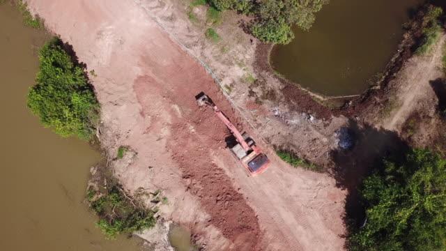 aerial bagger bagger graben constrution landstraße nahe fluss - bagger stock-videos und b-roll-filmmaterial