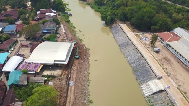 vídeos de stock, filmes e b-roll de aerial escavadeira retroescavadeira escavando constrution barragem do rio - ouro metal