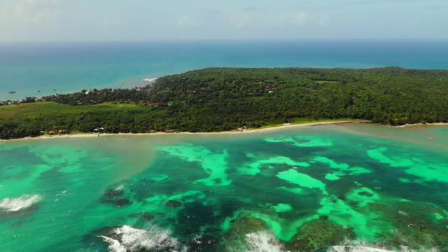 stockvideo's en b-roll-footage met aerial exit: forest covered island surrounded by bright ocean, rocky shallows - little corn island, nicaragua - eiland