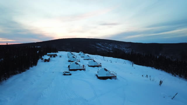 aerial exit: igloos on snowy plain, forest covered valley, fairbanks, alaska - igloo stock videos & royalty-free footage