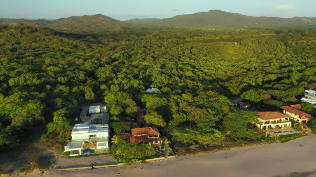 aerial exit: luscious, tree covered valley in evening sun by ocean shore - el gigante, nicaragua - ニカラグア点の映像素材/bロール