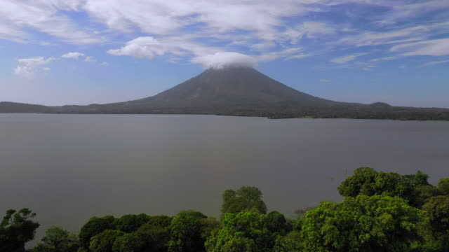 aerial exit: trees on edge of ocean with volcano, smoke on opposite side - ometepe, nicaragua - nicaragua stock-videos und b-roll-filmmaterial