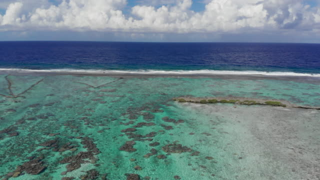 aerial exit: vibrant blue tropical waves crashing on shallow shore in vahine, french polynesia - shallow stock videos and b-roll footage