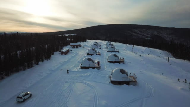 aerial exit/ascend: igloo homes on snowy plain by forest valley, fairbanks, alaska - valley stock videos & royalty-free footage