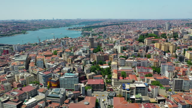 aerial: famous galata tower next to beautiful bosphorus strait - istanbul, turkey - galataturm stock-videos und b-roll-filmmaterial