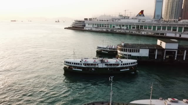 aerial: ferry coming in to dock as another leaves, victoria harbor, hong kong - 客船点の映像素材/bロール