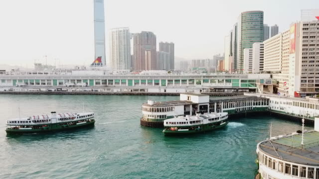 stockvideo's en b-roll-footage met aerial: ferry leaving pier as another comes in, victoria harbor, hong kong - star ferry