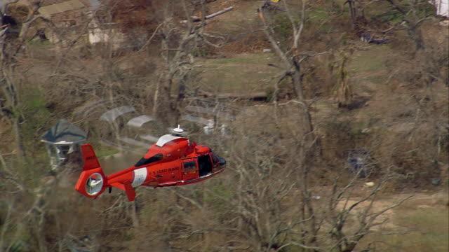 aerial fire patrol aerospatiale dauphin helicopter flying over ruined neighborhood / waveland, medium shot - 2005年点の映像素材/bロール