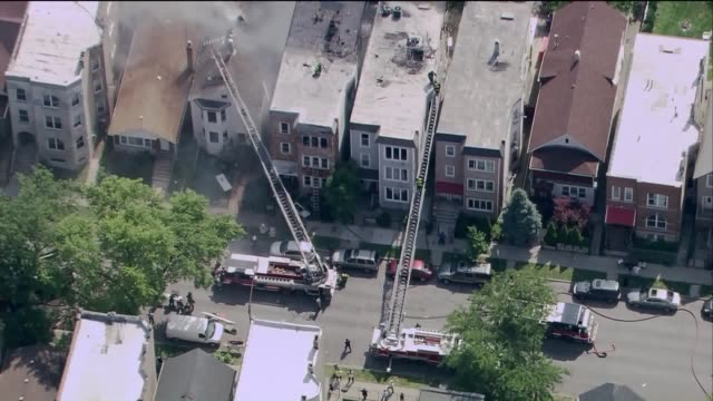 wgn aerial firefighters on roofs of apartment buildings on fire in chicago's logan square neighborhood on july 5 2017 - logan circle stock videos and b-roll footage