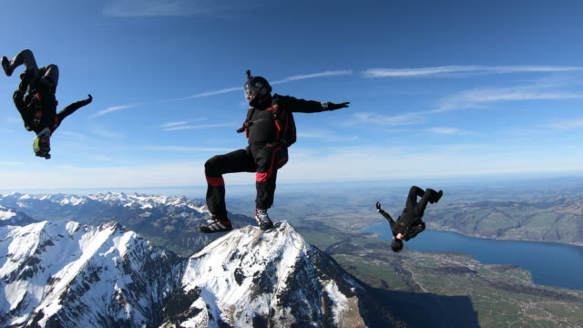 aerial first person view of skydiving in switzerland with team mates - three people stock videos & royalty-free footage