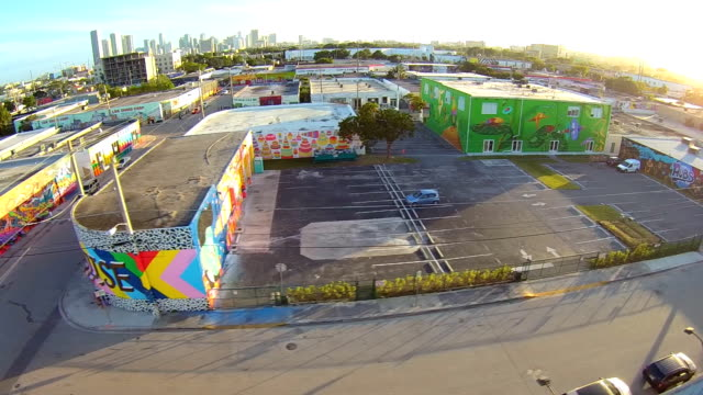 aerial flight across wynwood art district, hand painted buildings in miami florida. - stadtviertel stock-videos und b-roll-filmmaterial
