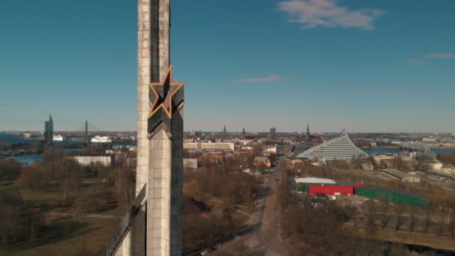 aerial flight around victory monument on sunny day with riga in background. soviet architecture after world war 2 - eternity stock videos & royalty-free footage