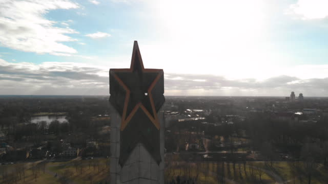 aerial flight away from victory monument (top star) on sunny day in riga. soviet architecture after world war 2 - eternity stock videos & royalty-free footage