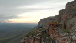 Aerial - flight forward past sitting on vacation adult woman with a backpack sits and rests of the rock at the foot of the epic plateau at sunset. View from the back. Russia. North Caucasus