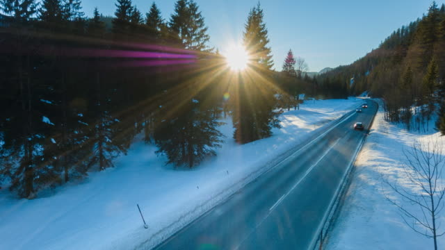 aerial flight over forest and rural road covered in snow in winter - ländliche straße stock-videos und b-roll-filmmaterial