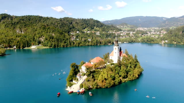 aerial / flight over lake bled, bled island with church of the assumption of the virgin mary - slowenien stock-videos und b-roll-filmmaterial