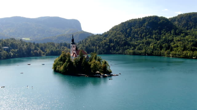 aerial / flight over lake bled in slovenia/ top view of the church of the assumption of the virgin mary - lago di bled video stock e b–roll