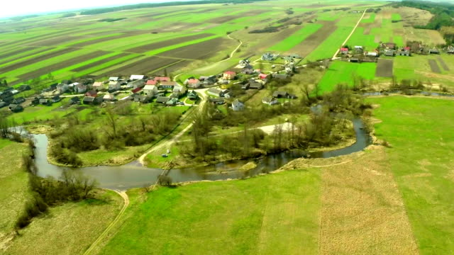 Aerial flight view of a green natural village and river
