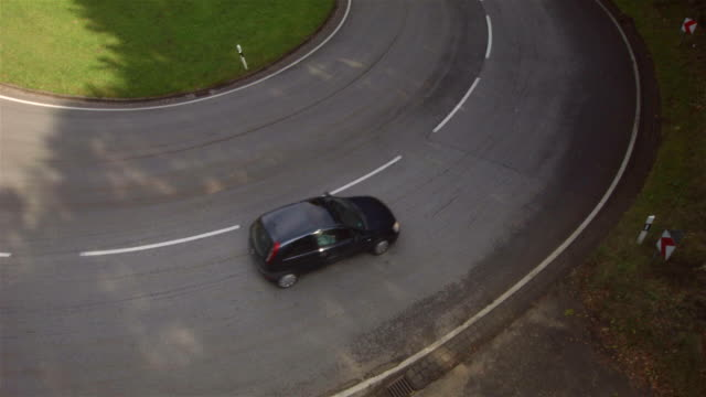 aerial flight view of traffic going trough tight bend in rural road - biegung stock-videos und b-roll-filmmaterial