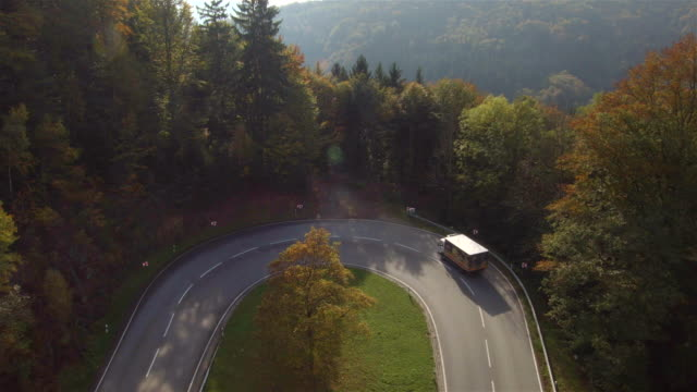 Aerial flight view of truck going trough tight bend in rural road