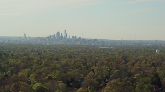 Aerial floating over lush green trees with Philadelphia skyline on the horizon