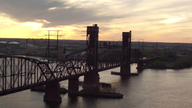 Aerial floating over railroad bridge with sun setting in the distance