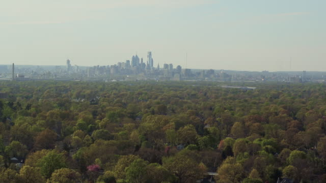 Aerial floating over treetops away from the Philadelphia skyline in the distance