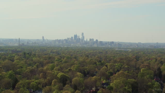 aerial floating over treetops with philadelphia skyline in the distance - distant stock videos & royalty-free footage