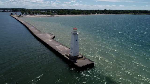aerial fly around of  lighthouse and breakwall entrance to harbor on lake ontario - ontariosee stock-videos und b-roll-filmmaterial