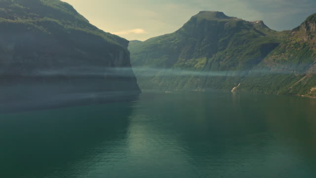 aerial fly over mist over tranquil water in the fjord of geiranger with hills in the background - landscape scenery stock videos & royalty-free footage