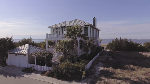 drone. aerial fly-by of luxury two-story seaside bald head island beach house with view of ocean in the distance on a sunny summer day. - beach house stock videos & royalty-free footage