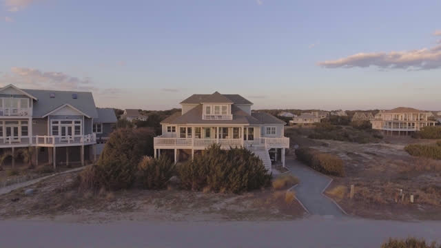 drone. aerial fly-by of luxury two-story seaside beach houses in sleepy beach town at sunrise. - beach house stock videos & royalty-free footage
