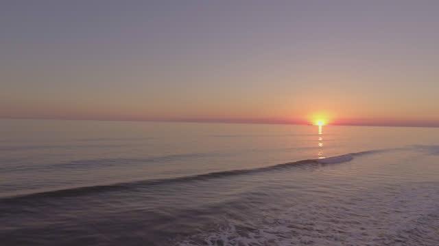 vídeos y material grabado en eventos de stock de zángano. sobrevuelo aéreo de las olas del océano que se estrellan en la costa mientras un barco pasa frente al sol en el horizonte al amanecer. - embarcación de pasajeros