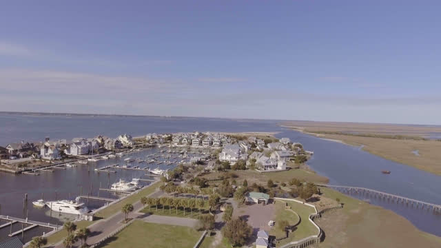 drone. aerial fly-by over of boats docked at bald head island marina and luxury seaside beach houses on sunny summer day. - bald head island stock videos & royalty-free footage